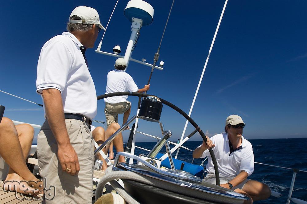 Sailors at helm of sailboat