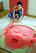 Chinese artist Yu Chen poses next to one of her works-in-progress at her Beijing apartment June 5, 2003.