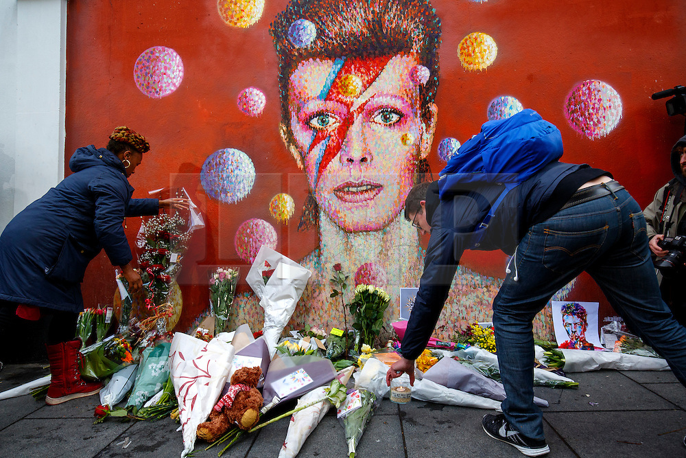 © Licensed to London News Pictures. 11/01/2016. London, UK. David Bowie fans paying their respects at his mural in Brixton, where he was born, in south London on Monday, 11 January 2016. Music legend David Bowie died aged 69, after suffering from cancer. Photo credit: Tolga Akmen/LNP