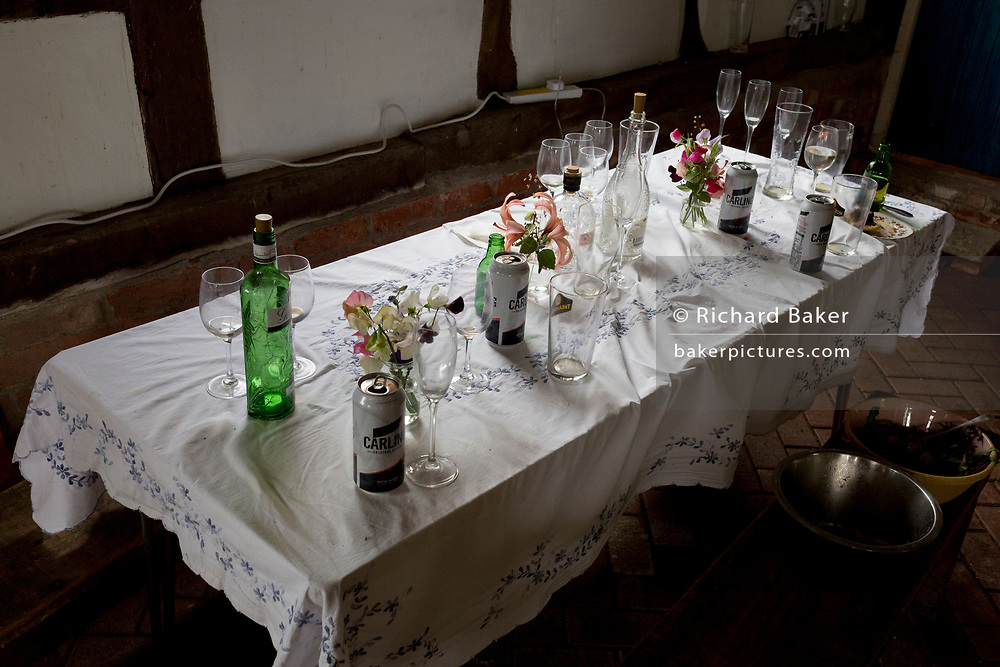 The aftermath debris of glasses and beer cans at dawn, the morning after a 50th birthday party, spread across a barn table in the Herefordshire countryside, on 23rd June 2019, in Kington, herefordshire, England.