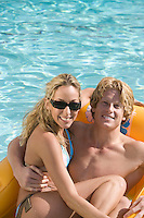 Portrait of Young Couple on Inflatable Raft in Pool