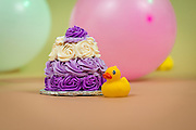 Small birthday cake with balloons and rubber duck.