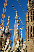 Sagrada Familia by Antoni Gaudi. Passion Facade towers (l.), construction works in the Nave, and a Nativity Facade tower (r.).