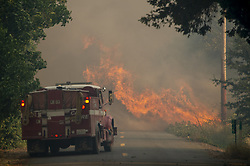 July 31, 2018 - Lakeview, California, U.S. - A Cal Fire truck waits as the flames cross Hendricks Road, east of the town of Lakeview on Tuesday, July 31, 2018 in Clearlake.  Mendocino Complex fires had burned 90,212 acres by Wednesday morning, Cal Fire said. (Credit Image: © Jose Luis Villegas/Sacramento Bee via ZUMA Wire)
