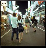 Young Tokyoites out for the evening in Kabuki-Cho entertainment district, restaurant district and Asia's largest red light district.  All exist together and young people flood to restaurants for the good food and energy of the area. Shinjuku, Tokyo, Japan.