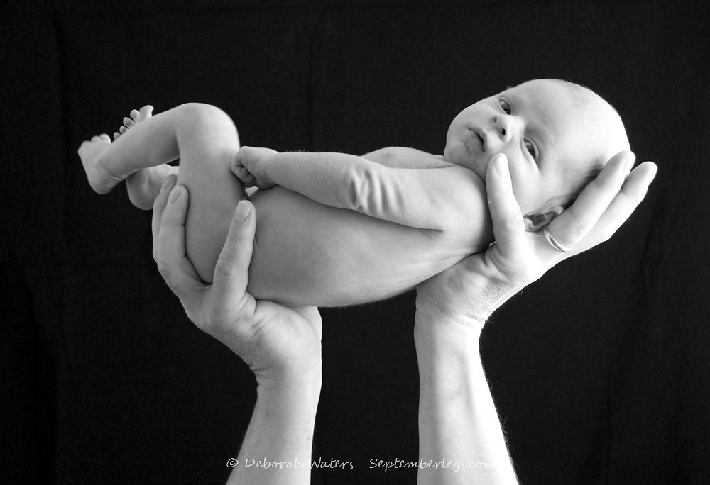 Newborn baby boy aged 9 days held up in the hands of his father, Black & white image isolated on black
