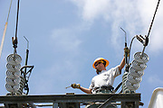 "Utility workman installing updated components to a ""city gate"" electrical substation Linemen working on a city gate"