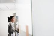 Female office worker standing in office doorway side view