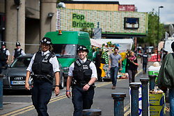 © Licensed to London News Pictures. 23/07/2015. London, UK. Police patrol the streets of Brixton before British home Secretary Theresa May delivers a speech on the relationship between police and the community at Brixton Recreation Centre in Brixton, south London.  Photo credit: Ben Cawthra/LNP