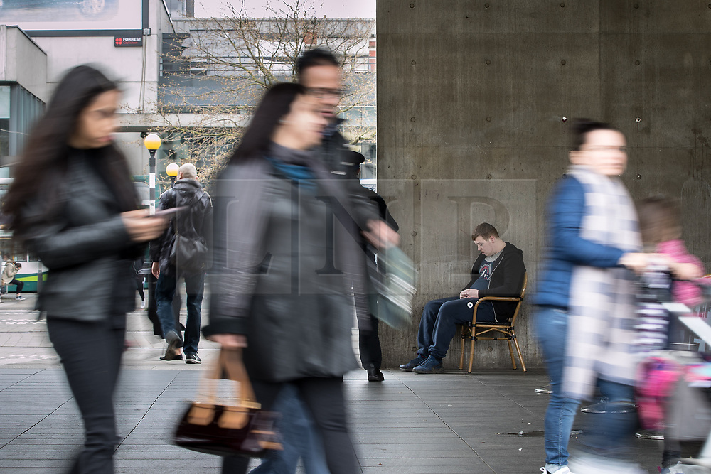 © Licensed to London News Pictures . 06/04/2017 . Manchester , UK . A man sits slumped in a chair , watched over by two PCSOs , next to Caffe Nero in Piccadilly Gardens . An epidemic of abuse of the drug spice by some of Manchester's homeless population , in plain sight , is causing users to experience psychosis and a zombie-like state and is daily being witnessed in the Piccadilly Gardens area of Manchester , drawing large resource from paramedic services in the city centre . Photo credit : Joel Goodman/LNP