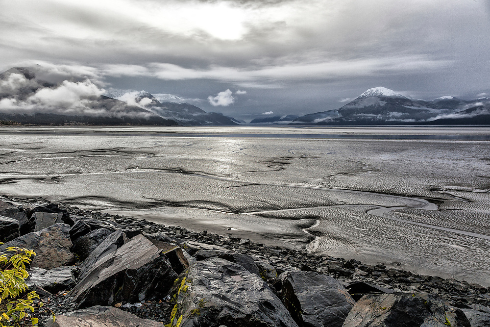 Alaska.  Wide-angle view of the Turnagain Arm mud flats near Girdwood on a stormy day in September with the sun breaking through a heavily overcast sky.  New snow is visible on the tops of the mountains in the background.