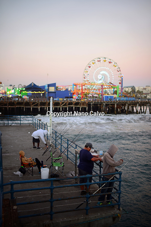 Group of people fishing from Santa Monica Pier, California.