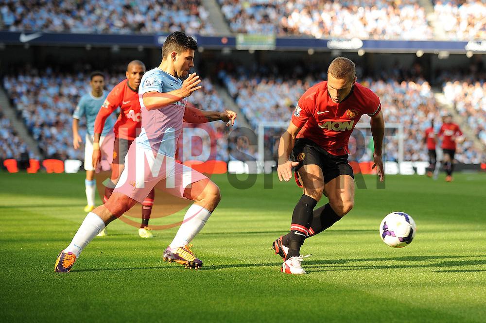 Manchester City's Sergio Aguero takes on Manchester United's Nemanja Vidic - Photo mandatory by-line: Dougie Allward/JMP - Tel: Mobile: 07966 386802 22/09/2013 - SPORT - FOOTBALL - City of Manchester Stadium - Manchester - Manchester City V Manchester United - Barclays Premier League