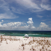 Wide shot of Pensacola Beach, Florida with single sunshade on the beach, tropical clouds on the horizon and oat grasses in foreground.