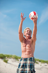 In shape older man playing volleyball at the beach in East Hampton,NY