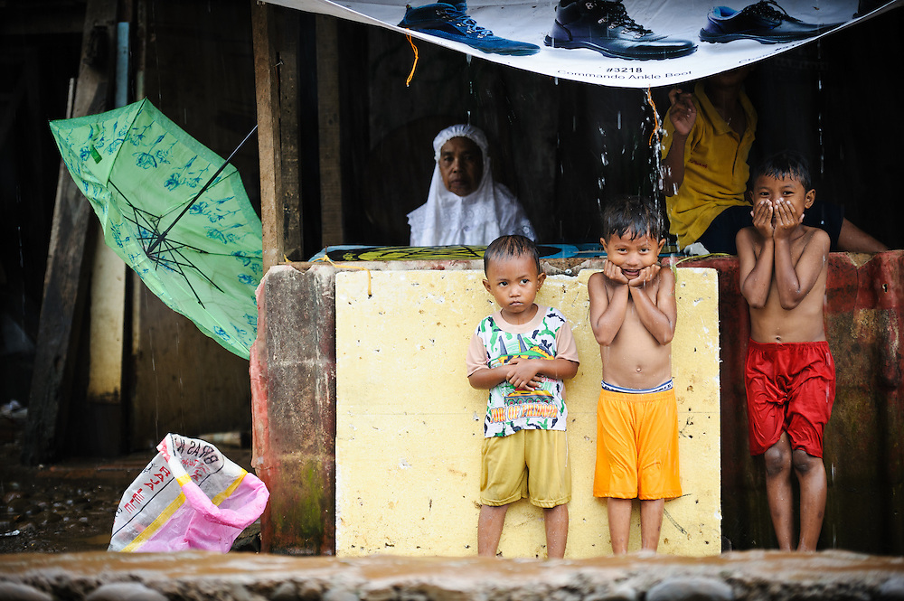 Children sheltering from the rain outside the school supported by the Sacred Childhoods Foundation, Makassar, Sulawesi, Indonesia.