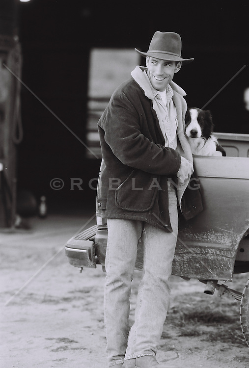 Man leaning against a pick up truck with a dog