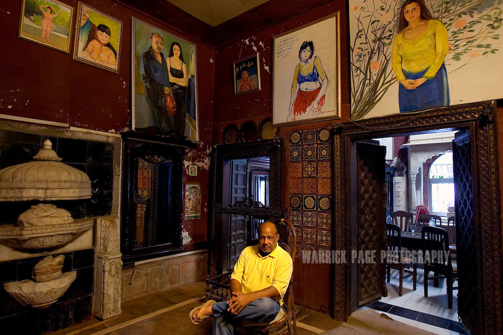 "LAHORE, PAKISTAN - AUGUST 14: Controversial Pakistani artist, Iqbal Hussain, sits amongst a collection of his paintings in his haveli/restaurant, August 14, 2006, Lahore, Pakistan. Iqbal grew up in Lahore's red-light district in a brothel with his mother who worked as a ""dancing girl"". Iqbal fell into crime quickly as a youth until his late teens when a chance meeting led him to study painting at the National College of Arts. Breaking free of the more traditional South-Asian style, Iqbal focused his work on painting portraits (including nude) of prostitutes and landscapes of the red-light district. Iqbal has received death threats from hard-line Islamic leaders for displaying his paintings of naked women. His work has since gained acclaim around the world with some of his works auctioned at Sothebys. (Photo by Warrick Page)"