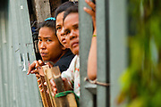 16 MAY 2010 - BANGKOK, THAILAND: A Thai family watches for snipers from the gate in front of their home on Rama IV Road in Bangkok Sunday. Thai troops and anti government protesters clashed on Rama IV Road again Sunday afternoon in a series of running battles. Troops fired into the air and unidentified snipers shot at pedestrians on the sidewalks. At one point Sunday the government said it was going to impose a curfew only to rescind the announcement hours later. The situation in Bangkok continues to deteriorate as protests spread beyond the area of the Red Shirts stage at Ratchaprasong Intersection. Many protests now involve people who have not been active in the Red Shirt protests and live in the vicinity of Khlong Toei slum and Rama IV Road. Red Shirt leaders have called for a cease fire, but the government indicated that it is going to go ahead with operations to isolate the Red Shirt camp and clear the streets.      PHOTO BY JACK KURTZ