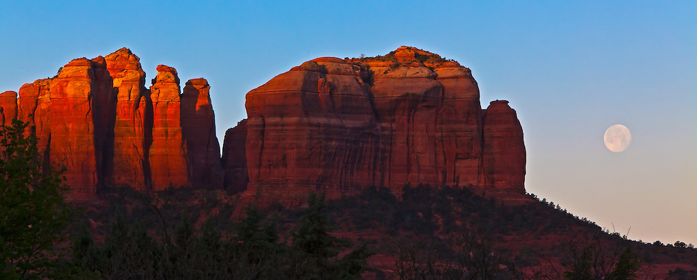 The rising sun illuminates the eastern flank of Cathedral Rock in Sedona, Arizona as the full moon sets.