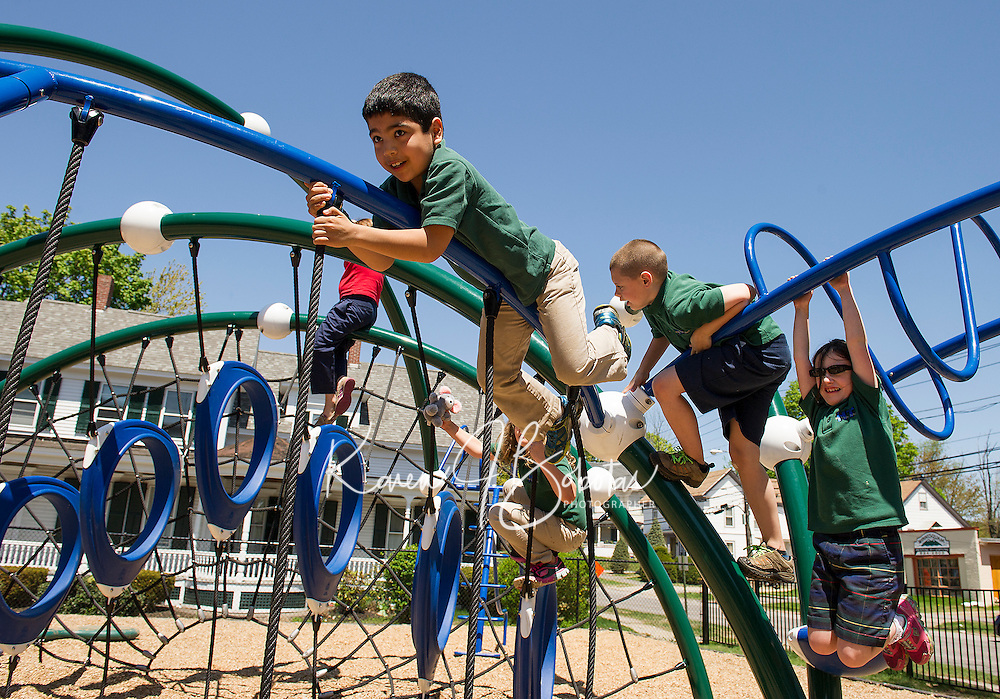 Holy Trinity first, second and third graders get to hang around at recess in a very active way inside their playground area off Messer Street.    (Karen Bobotas/for the Laconia Daily Sun)