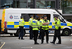 © Licensed to London News Pictures. 09/10/2019. London, UK. Police officers from the Kent Constabulary (front) stand with colleagues from the Metropolitan Police outside The Home Office as Extinction Rebellion activists take part in a third day of protests in central London. The climate change group intend to blockade the Westminster area for two weeks to demand that the government takes immediate and decisive action on climate change. Photo credit: Peter Macdiarmid/LNP