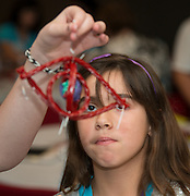"""Students from Woodson Middle School check out a model of an eye that they created from licorice sticks during an """"Introduce a Girl to Engineering"""" workshop at ExxonMobil, February 19, 2014."""