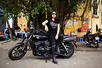 A portrait of Bui Thi Thu Huyen on her 750cc Harley Davidson motorcycle in the Old Quarter of Hanoi, Vietnam.