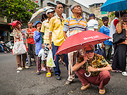 "17 FEBRUARY 2015 - BANGKOK, THAILAND:  People wait in line for the Chinese New Year food distribution to start at the Poh Teck Tung Foundation in Bangkok. Chinese New Year is February 19 in 2015. It marks the beginning of the Year of Sheep. The Sheep is the eighth sign in Chinese astrology and the number ""8"" is considered to be a very lucky number. It symbolizes wisdom, fortune and prosperity. Ethnic Chinese make up nearly 15% of the Thai population. Chinese New Year (also called Tet or Lunar New Year) is widely celebrated in Thailand, especially in urban areas like Bangkok, Chiang Mai and Hat Yai that have large Chinese populations.      PHOTO BY JACK KURTZ"