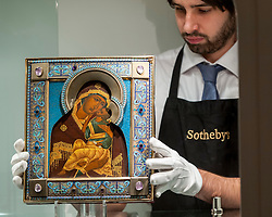 "© Licensed to London News Pictures. 25/11/2016. London, UK. A technician examines ""A Fabergé gem-set silver-gilt and enamel icon of the Yaroslavskaya Mother of God"" (est. GBP 30-50k), at the preview of artworks from Sotheby's upcoming Russian sales in New Bond Street, where over three hundred works spanning several centuries will be offered. Photo credit : Stephen Chung/LNP"