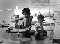 BURMA (MYANMAR) Yangon Division, Yangon. 2006. Sisters sit in the shade near the Yangon River ferry crossing. For too many Burmese children there is simply not enough to eat.