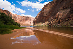 Glen Canyon, Arizona:  A single raft makes its way south towards the mouth of Glen Canyon, near the end of a 15 mile float trip on the Colorado River below Glen Canyon Dam.   Trip guided by Wilderness River Adventures (managed by ARAMARK), the only operator (2006) permitted between the dam and Lees Ferry (take-out).  Additional views, both horizontal and vertical, with different horizon placements available.