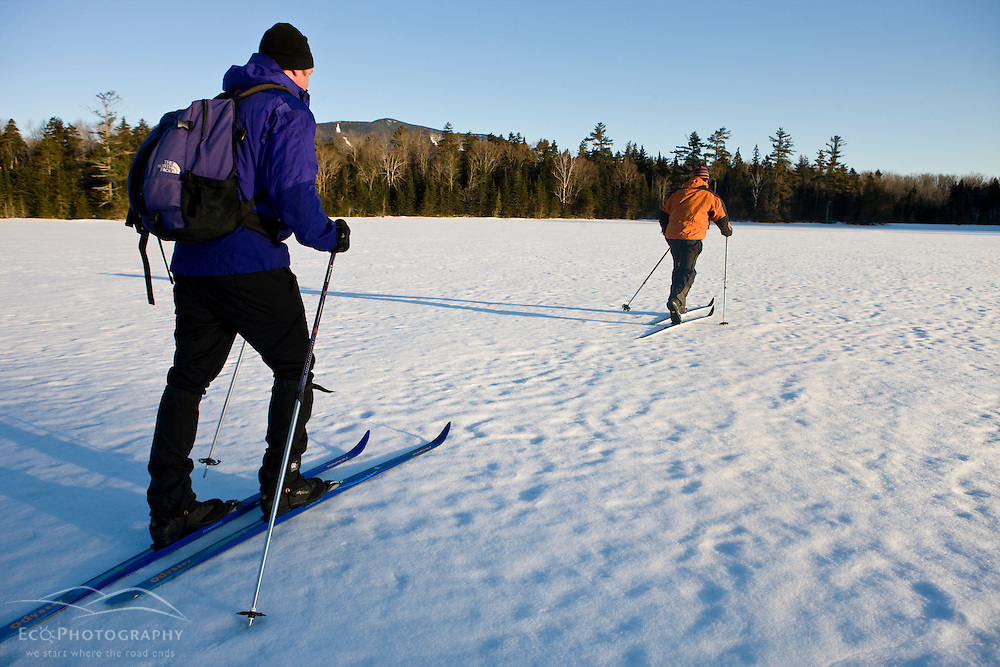 Cross-country skiers on a frozen pond near Little Lyford Pond Camps near Greenville, Maine, Winter.  Baker Mountain is in the distance.