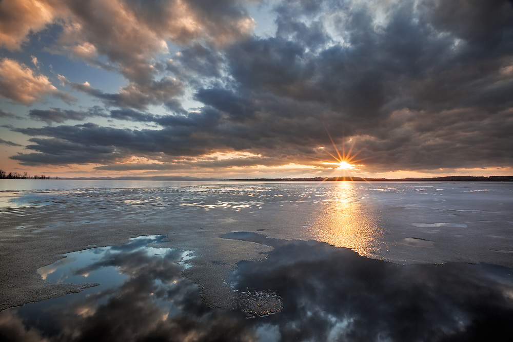 Ice breaking up on Lake Champlain, sunset and colorful clouds, Sand Bar State Park, South Hero, Vermont