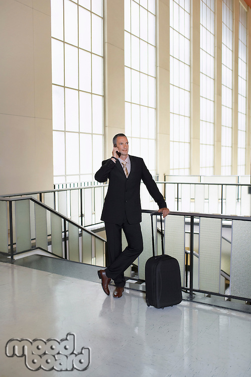 Business man using mobile phone in airport lobby
