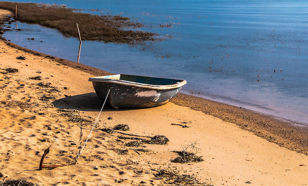 Small boat anchored at a deserted sandy beach in Cape Cod, Massachusetts.