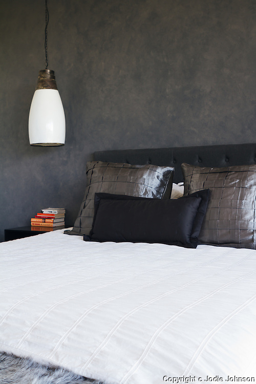 Masculine bedroom decor with dark grey painted feature wall and rustic pendant hanging light