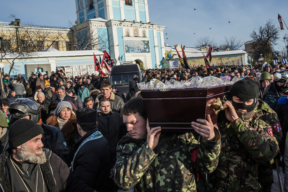 KIEV, UKRAINE - JANUARY 26: Men carry a casket containing the body of Mikhail Zhiznevsky, 25, an anti-government protester who was killed in clashes with police, outside Mikhailovsky Cathedral after a memorial service there in his honor on January 26, 2014 in Kiev, Ukraine. After two months of primarily peaceful anti-government protests in the city center, new laws meant to end the protest movement have sparked violent clashes in recent days. (Photo by Brendan Hoffman/Getty Images) *** Local Caption ***