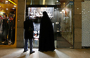 Two young friends, demonstrate the range of conformity,  one wears a traditional chador and the other a more modern manteau. They shop at the upscale Tandis Center which boasts the most fashionable and expensive stores in Tehran.