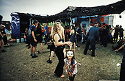 A young girl in a face mask dancing with people in front of a sound system. Glastonbury 1995.