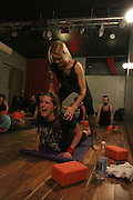 NEW YORK CITY, NEW YORK, MARCH 30, 2016. Caryn Havlik gets a readjustment by Metal Bones Yoga instructor Saskia Thode. The class takes place at 6:30 p.m. on Wednesdays at The Cobra Club in Bushwick, Brooklyn. 03/30/2016. Photo by Donna M. Airoldi/NYC News Service