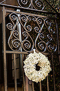 Decorative iron gates with popcorn berry wreath at a historic home in Charleston, SC.