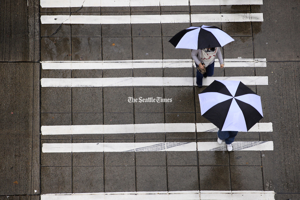 Pedestrians walk with umbrellas near 3rd Avenue on a rainy day in Seattle. <br />