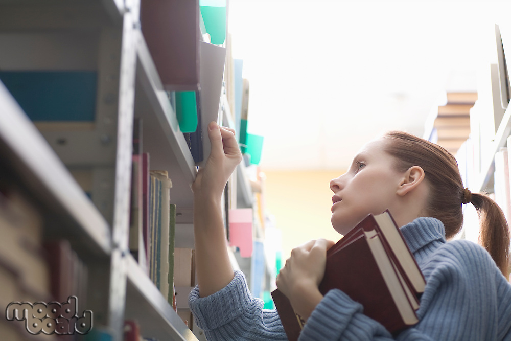 Young woman references library books on shelves