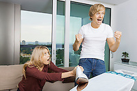 Cheerful man cheering while shocked woman at the ironing board in living room