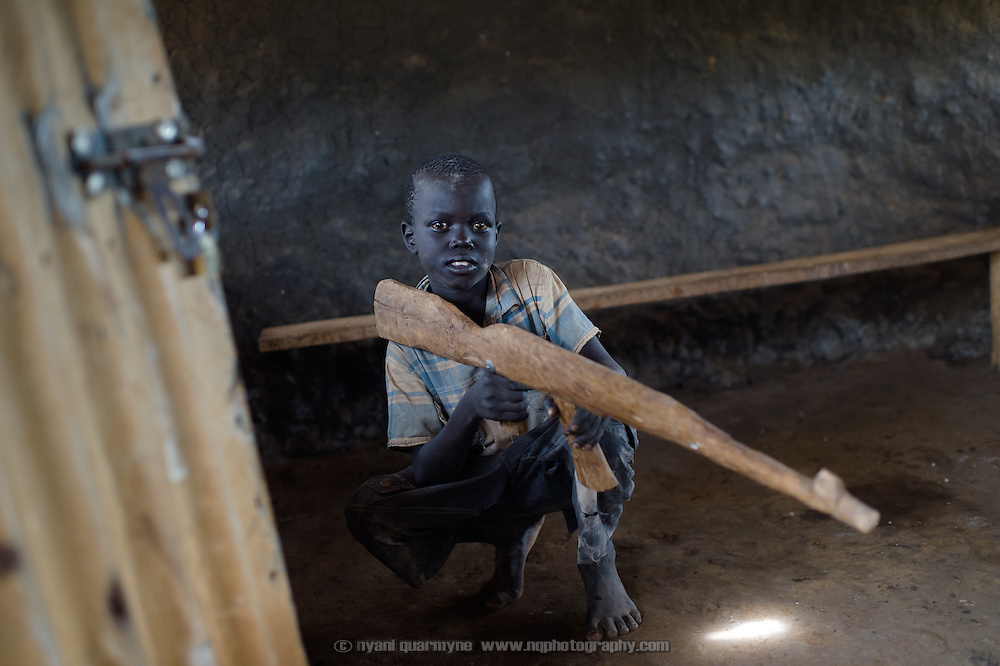 Emmanuel Ohisa with a toy AK-47 rifle made from wood in the village of Kudo in Eastern Equatoria in South Sudan on 8 August 2014. The proliferation of small arms compounds the threats to lasting peace in South Sudan.