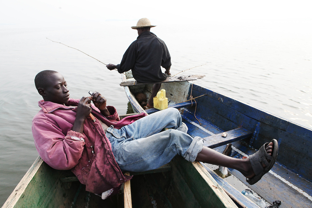Augustino Ssekisaka (left) and Siggando Francis spend the morning fishing on Lake Victoria. Here in Ggaba, a small town in southern Uganda that almost entirely subsists on the fishing industry, the locals have contributed to the dangerous overfishing of the lake despite strict regulations from Tanzania, Uganda, and Kenya. Fishermen continue to keep fish that are far below the required minimum weight and employ dymanite and poison.