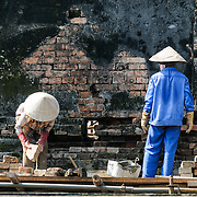 Workers renovate a damaged wall at the Imperial City in Hue, Vietnam. A self-enclosed and fortified palace, the complex includes the Purple Forbidden City, which was the inner sanctum of the imperial household, as well as temples, courtyards, gardens, and other buildings. Much of the Imperial City was damaged or destroyed during the Vietnam War. It is now designated as a UNESCO World Heritage site.