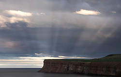 © Licensed to London News Pictures. <br /> 23/03/2015. <br /> <br /> Saltburn, United Kingdom<br /> <br /> Rays of light from the setting sun shine down through clouds onto the cliffs at Huntcliff in Saltburn, Cleveland.<br /> <br /> Photo credit : Ian Forsyth/LNP