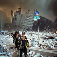 Rescue workers pick their way through the blasted landscape of downtown New York after the Twin Towers of the World Trade Center were destroyed by a terrorist attack.